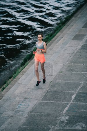 young sportswoman jogging on quay near river