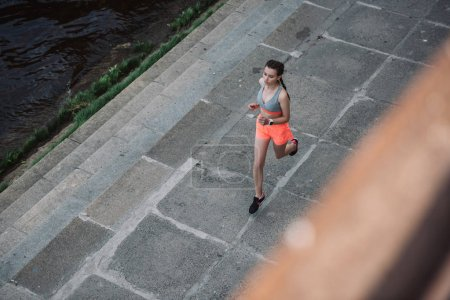overhead view of young sportswoman running in city