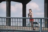 sportswoman using smartwatch near railings on bridge