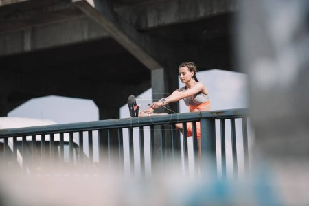 athletic girl stretching leg on railings on bridge