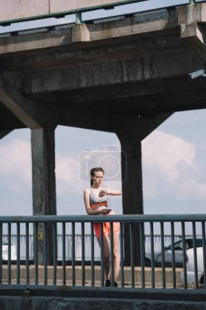 beautiful sportswoman looking at watch and standing on bridge