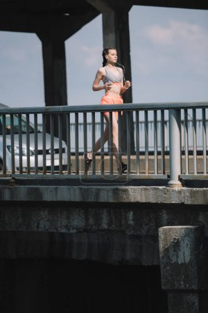 sportswoman running on bridge in city