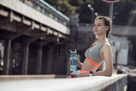 attractive sportive girl holding sports bottle with water and standing at railings