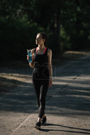 athletic woman holding sports bottle and walking on path in park