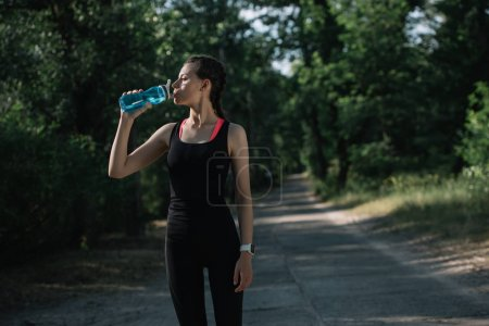 attractive sportswoman drinking water in park