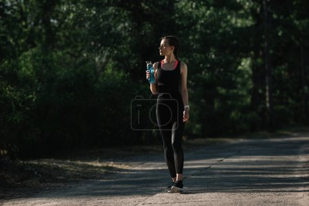 Photo for Athletic girl holding sports bottle with water and walking in park - Royalty Free Image