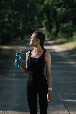 athletic woman holding sports bottle with water in park