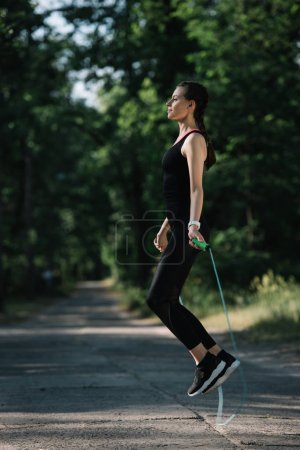 beautiful athletic girl jumping on skipping rope on path in park