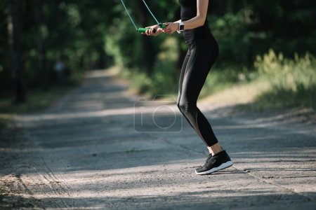 cropped view of athletic woman training with skipping rope on path in park