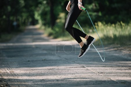 cropped view of sportswoman jumping on skipping rope in park