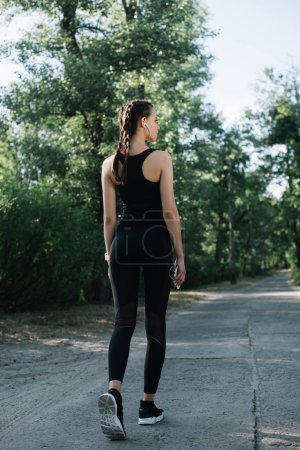 back view of woman in sportswear listening music with earphones and smartphone in park