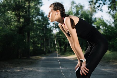 tired sportswoman listening music with earphones and smartphone