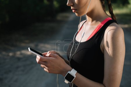 cropped view of young sportswoman with earphones, smartwatch and smartphone