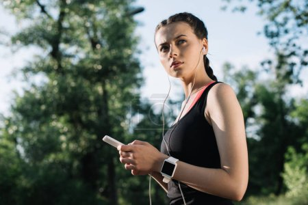beautiful sportswoman with smartwatch listening music with earphones and smartphone