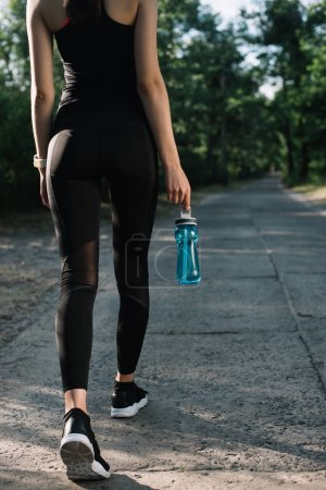 back cropped view of sportswoman with bottle of water walking on path