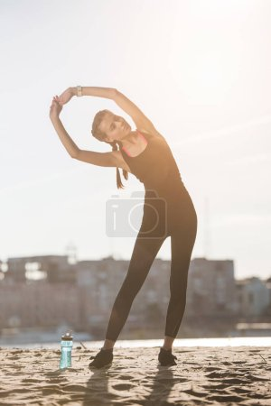 attractive sportswoman stretching on beach with sports bottle