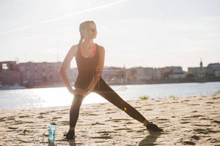 sportive qui s'étend de la jambe sur la plage avec Gourde de sport près de