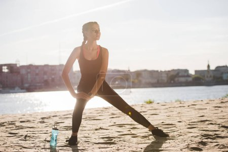 sportswoman stretching leg on beach with sports bottle near