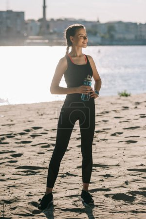 Photo for Beautiful sportswoman with water in sports bottle standing on beach - Royalty Free Image