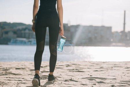 Photo pour Vue recadrée de sportive avec de l'eau en bouteille marchant sur la plage avec contre-jour - image libre de droit
