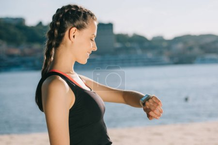 smiling sportswoman looking at smart watch on beach