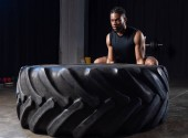 athletic african american man exercising with tyre and looking away in gym