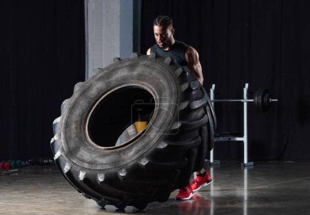 muscular young african american sportsman exercising with tire