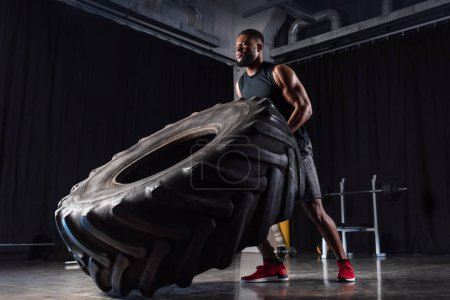 low angle view of muscular african american man training with tyre and looking away