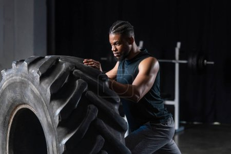 focused young african american sportsman training with tyre in gym
