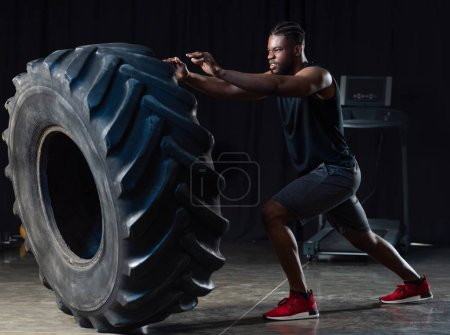 side view of muscular african american sportsman exercising with tyre