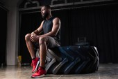 low angle view of pensive african american sportsman sitting on tyre and looking away