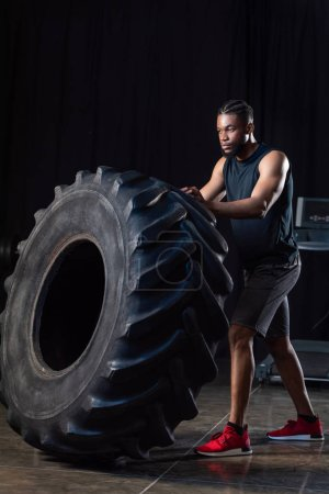 full length view of athletic african american man training with tyre and looking away
