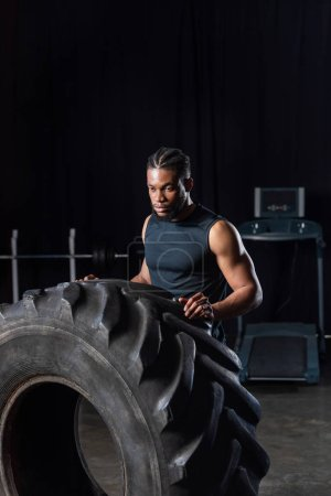 serious muscular african american sportsman exercising with tyre