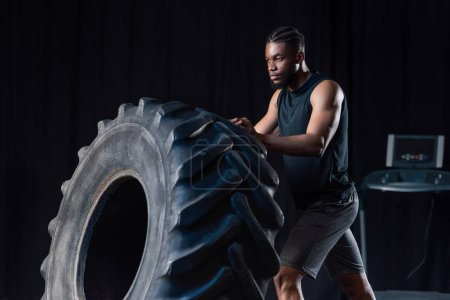 serious african american sportsman training with tire and looking away