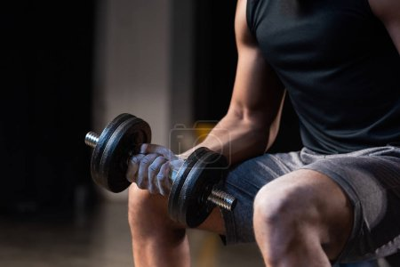 cropped shot of muscular african american man training with dumbbell