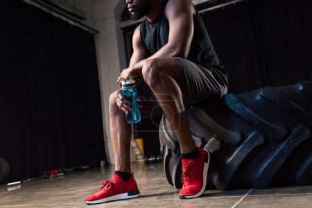 Photo for Cropped shot of young african american sportsman sitting  tyre and holding bottle of water in gym - Royalty Free Image
