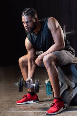 muscular african american sportsman sitting on tyre and exercising with dumbbell
