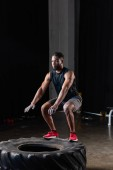 full length view of athletic african american man in sportswear exercising with tyre in gym