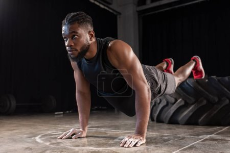 athletic african american man looking away while doing push ups and training with tyre