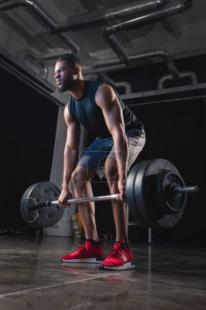 low angle view of muscular african american sportsman lifting barbell and looking away in gym