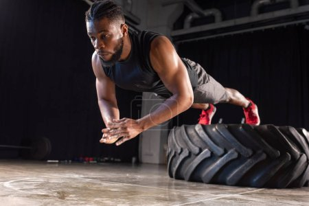 Photo for Muscular african american sportsman exercising with tyre - Royalty Free Image