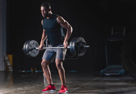 athletic african american man in sportswear lifting barbell and looking away in gym