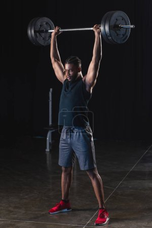 full length view of muscular african american sportsman lifting barbell in gym