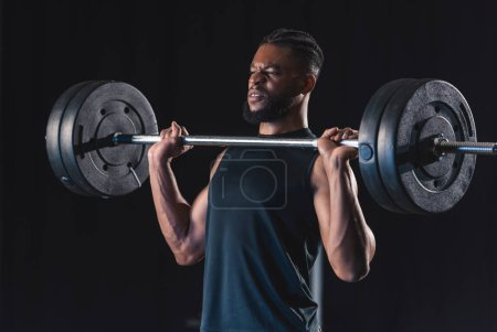 Photo for Muscular african american sportsman lifting barbell on black - Royalty Free Image