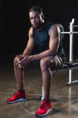 full length view of young african american sportsman sitting and looking at camera in gym