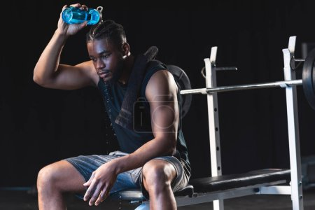 sweaty african american sportsman pouring water on head after workout in gym