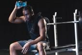 sueur sportif afro-américain, verser de l'eau sur la tête après la séance d'entraînement en gymnase