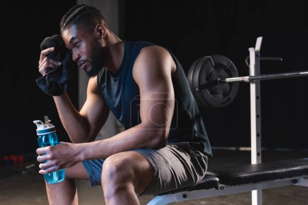 tired african american sportsman holding towel and bottle of water while sitting in gym