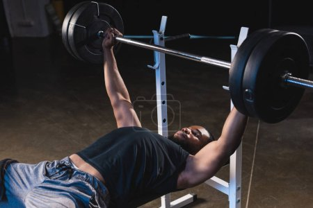 muscular african american sportsman lifting barbell in gym