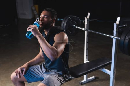 young african american sportsman drinking water and looking away in gym